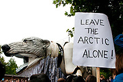 London, England, UK. The crowd greet  Aurora, the double-decker-bus-size polar bear puppet specially commissioned by Greenpeace to lead an Arctic-inspired street parade to the London HQ of oil giant Shell on 15 September. The three-tonne marionette bear is operated from the inside by a team of 15 puppeteers,  and  hauled on ropes by 30 volunteers along a route from Victoria Gardens to Shell's HQ at Waterloo. The giant bear, which is made of replica and reclaimed ship parts as well as recycled materials, carries in her fur the names of over 3 and half million people who have joined the global movement to protect the Arctic from industrial exploitation. This parade  was part of a global day of action to protect the Arctic withtens of thousands of people taking to the streets in over 70 cities worldwide. A protester holds a placard saying 'Leave the Arctic Alone'.