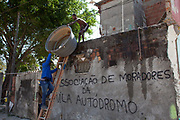 Augusto Periera and son take out his final belongings before his home is demolished. His house is one of the last standing of the original homes, is demolished today. Vila Autodromo favela, in the west zone of Rio, is in direct site of the Rio 2016 Olympic park. There has been an ongoing struggle between residents and the City Government of Eduardo Paes. After a long battle, 20 families who held on were allowed to stay, on the provision that they moved into houses constructed by the state, in the same style as the public housing programme.