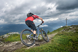 Rear view of mountain biker riding on uphill, Trentino-Alto Adige, Italy