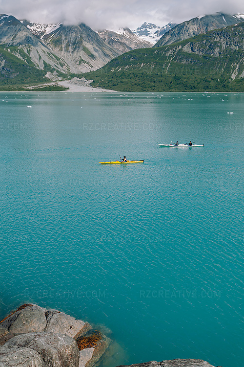 A group of kayaks paddling in Tarr Inlet in southeast Alaska's Glacier Bay National Park and Preserve. Grand Pacific Glacier can be seen in the background (center frame). Photo © Robert Zaleski / rzcreative.com<br /> —<br /> To license this image contact: robert@rzcreative.com