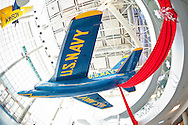 """Grumman F11 (F-11) Tiger jet, with big red ribbon attached, and suspended from ceiling of vast atrium of Cradle of Aviation, Long Island air and space Museum, on December 2, 2011. 180 degree fish eye lens view of 3 floor atrium showing complete aircraft and surroundings. Museum Row in Garden City, New York, USA. """"U.S. NAVY"""" printed in yellow on blue plane."""