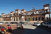 White taxi cars outside historic railway station building, Jerez de la Frontera, Spain