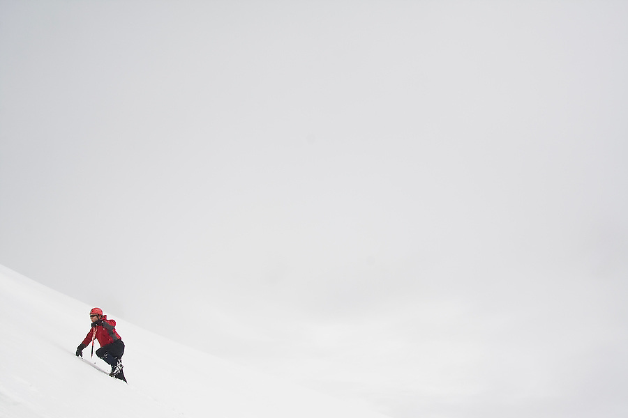 """A member of the University of Washington Climbing Club attending """"Snow School"""" ascends a snow slope at Paradise in Mount Rainier National Park, Washington. At the annual club event, members practice essential skills like glacier crevasse rescue and self arrest."""