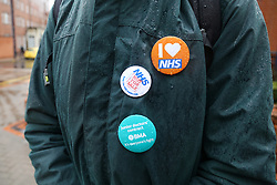 © Licensed to London News Pictures. 09/03/2016. Leeds, UK. An NHS supporter shows their badges outside Leeds General Infirmary in West Yorkshire at the start of 48-hour walkout by junior doctors. This, the longest strike so far, comes after the government announced it would impose the new contracts upon junior doctors after negotiations broke down.  Photo credit : Ian Hinchliffe/LNP