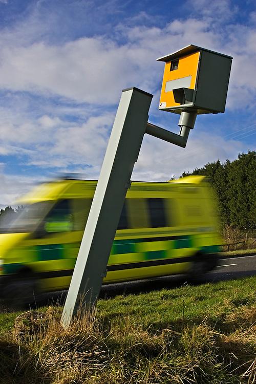 Ambulance passes vandalised Gatso speed camera on A40, Oxfordshire, England, United Kingdom