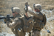 LCpL. Sterr, right, removes a duct-taped bundle of C-4 for use in breaching razor wire during live-fire exercises for the 2nd Battalion, 5th Marine Regiment at Camp Pendleton.