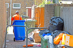 © Licensed to London News Pictures 29/07/2021. Bexley, UK. A refuse collector who is not on strike walking down an alleyway of rubbish. Household waste continues to pile up in the London borough of Bexley as binmen announce new strike dates in August. The workers have already been on strike for weeks and are striking over pay and victimisation of staff but employer Serco has failed to enter into negotiations. Photo credit:Grant Falvey/LNP