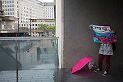 Tourist with a pink umbrella trying to read a map under cover from the rain. The South Bank is a significant arts and entertainment district, and home to an endless list of activities for Londoners, visitors and tourists alike.