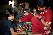 A family is decorating glass bracelets on their doorstep in the slum surrounding Firozabad, renowned as the 'glass city', in Uttar Pradesh, northern India. Due to extreme poverty, over 20.000 young children are employed to complete the bracelets produced in the industrial units. This area is considered to be one of the highest concentrations of child labour on the planet. Forced to work to support their disadvantaged families, children as young as five are paid between 30-40 Indian Rupees (approx. 0.50 EUR) for eight or more hours of work daily. Most of these children are not able to receive an education and are easily prey of the labour-poverty cycle which has already enslaved their families to a life of exploitation. Children have to sit in crouched positions, use solvents, glues, kerosene and various other dangerous materials while breathing toxic fumes and spending most time of the day in dark, harmful environments. As for India's Child Labour Act of 1986, children under 14 are banned from working in industries deemed 'hazardous' but the rules are widely flouted, and prosecutions, when they happen at all, get bogged down in courts for lengthy periods. A ban on child labour without creating alternative opportunities for the local population is the central problem to the Indian Government's approach to the social issue affecting over 50 million children nationwide.