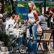 NLD/Amsterdam/20100612 - Nikkie Plessen en partner Ruben Bontekoe genietend van de zon op een terras in Amsterdam met hun pasgeboren baby