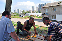 Agricultural workers enjoy a Saturday morning game of backgammon near the Salt Pier, where river boats moor in St. Petersburg, Russia. A massive complex of new apartments rises behind them.