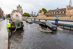 © Licensed to London News Pictures. 06/10/2019. London, UK. A contractor pumps water out of the road after flooding and excess surface water on Tower Bridge this morning following heavy rain and wet weather in the capital last night. Weather forecasts predict that most of the UK will be experience heavy rain and storms during the next few days. Photo credit: Vickie Flores/LNP