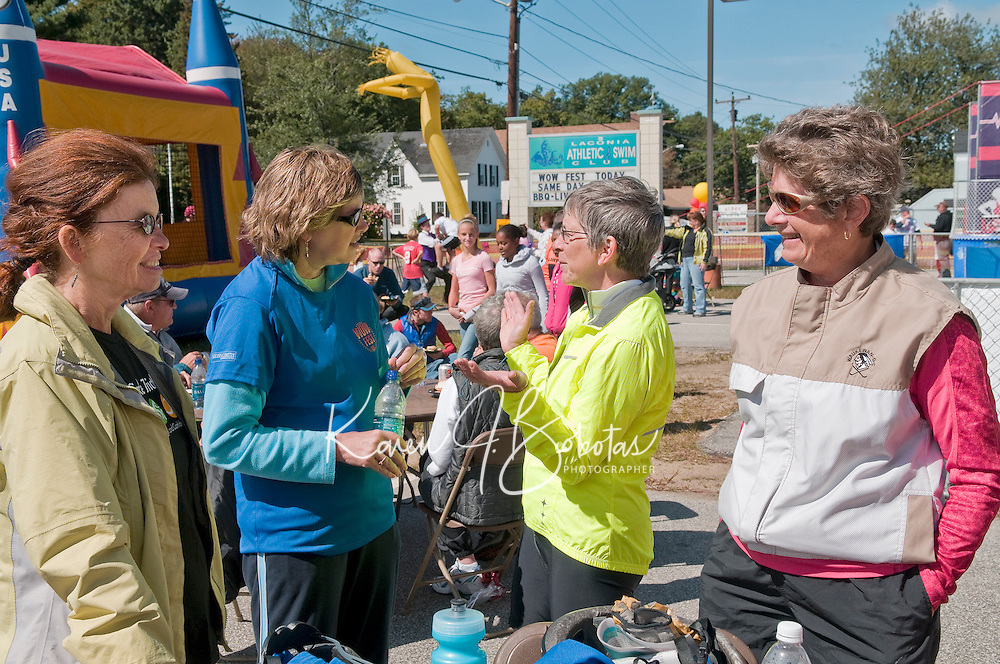 Marge Wilkinson (far left) and Marilyn Lynch (far right) enter the bbq tent after completing their 15 mile bike ride around Paugus Bay during the 1st annual WOW Fest event held at the Laconia Athletic and Swim Club Saturday afternoon.   (Karen Bobotas/for the Laconia Daily Sun)