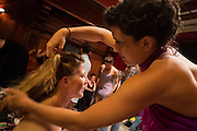 Lead dancer Jessica Grippo prepares another dancer's hair.