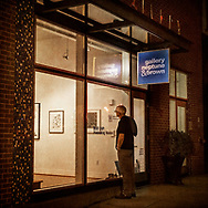 """A man pauses during his evening walk to check-out the art at a gallery on 14th Street. A dapper dandy makes his way up the street from grocery shopping -- perhaps eager to taste the goodies he just purchased. This image is from Robert Dodge """"Project: 14th and U Streets,"""" a look at the center of town in Washington, D.C. For info on publication or fine-art-, limited-edition prints, contact: Robert@RobertDodge.com."""