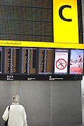 """An upright picture of a departures information board at Heathrow Airport's Terminal 5. A lady passenger stands motionless to read the details of flight departure times to echo that of a Vodafone advertisement containing a figure of a man standing erect on a beach, a generic scene of a person on holiday taking advantage of low mobile phone charges in mainland Europe.  Both the man and the woman are on opposite sides of the picture and we see a large letter C that denotes the check-in zone of this 400 metre-long terminal that has the capacity to serve around 30 million passengers a year. From writer Alain de Botton's book project """"A Week at the Airport: A Heathrow Diary"""" (2009). .."""