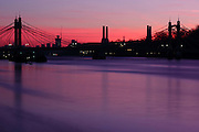 Long exposure shot of a red dawn sky with Albert Bridge and Battersea Power Station silhouetted in the background.