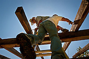 Bob Moss, left, unscrews structural bolts while Dennis Fenenbock, right, helps to support a loose beam at the long defunct Waldron Shelter in Farraugut State Park on Saturday.