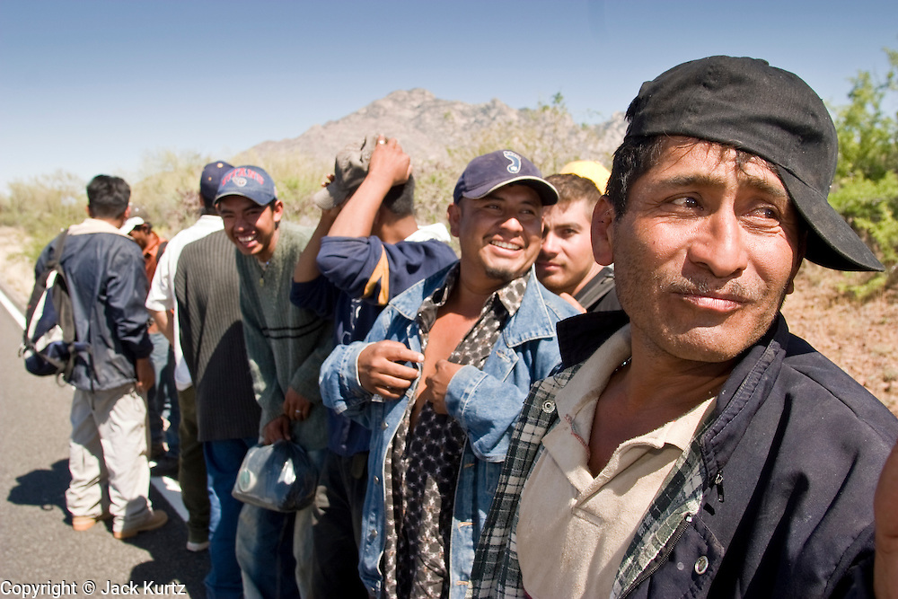 05 MAY 2003 -- SELLS, AZ: A group of 11 undocumented immigrants from Mexico mill about on the edge of AZ Highway 86 after being released by a Tohono O'Odham tribal police officer west of Sells, AZ, the capital of Tohono OOdham Indian Reservation, May 5, 2003. The men were passengers in van stopped for a traffic violation by the tribal police, who found the immigrants hiding inside. The driver of the van was arrested for driving without a license, no insurance and having false license plates. The Tohono OOdham reservation covers a vast expanse of Southern Arizona and has a 70 mile border with Mexico. In recent years the reservation has been flooded with undocumented immigrants who pass through the reservation on their way north to Phoenix, AZ, and other cities in the US. About 1,500 undocumented immigrants, most from Mexico, cross the reservation, which has more land than the state of Delaware,  every day. According to the tribal government, the tribal police department spends about 60 percent of its resources dealing with crime created by the undocumented immigrants. Many times tribal police officers have to wait hours for the US Border Patrol to respond to calls to pick up undocumented immigrants. The officer waited for more than an hour for Border Patrol to arrive on the scene and eventually released the immigrants. Border Patrol arrived minutes later and apprehended all of the immigrants.   PHOTO BY JACK KURTZ