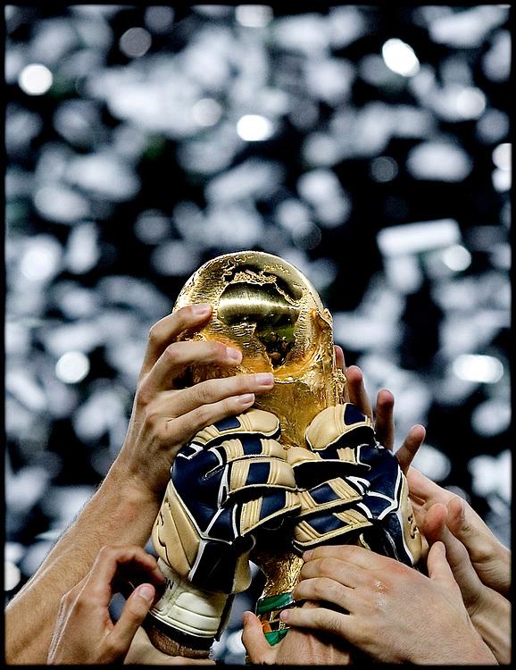 Duitsland. Berlijn, 09-07-2006<br /> WK Voetbal Finale: Italie-Frankrijk. <br /> Titelverdediger Frankrijk starte hoopvol tegen het altijd sterke Italie. Het had een mooi afscheid voor de franse voetballer moeten zijn maar Zinedine Zidane werd met een rode kaart van het veld werd gestuurd na het geven van een kopstoot aan Mazzarati. De fransen hielden lang stand maar na de verlenging en strafschoppen gingen de Italianen lachend met de Wereldbeker naar huis. Italiaanse handen houden de wereldbeker omhoog na de winst op medefinalist Frankrijk. <br /> Foto: Patrick Post / Sportstation