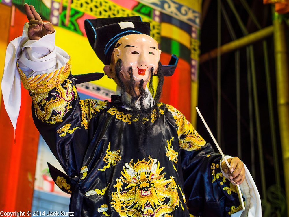 """18 AUGUST 2014 - BANGKOK, THAILAND:   Members of the Lehigh Leng Kaitoung Opera troupe perform at Chaomae Thapthim Shrine, a small Chinese shrine in a working class neighborhood of Bangkok. The performance was for Ghost Month. Chinese opera was once very popular in Thailand, where it is called """"Ngiew."""" It is usually performed in the Teochew language. Millions of Chinese emigrated to Thailand (then Siam) in the 18th and 19th centuries and brought their culture with them. Recently the popularity of ngiew has faded as people turn to performances of opera on DVD or movies. There are still as many 30 Chinese opera troupes left in Bangkok and its environs. They are especially busy during Chinese New Year and Chinese holiday when they travel from Chinese temple to Chinese temple performing on stages they put up in streets near the temple, sometimes sleeping on hammocks they sling under their stage. Most of the Chinese operas from Bangkok travel to Malaysia for Ghost Month, leaving just a few to perform in Bangkok.      PHOTO BY JACK KURTZ"""