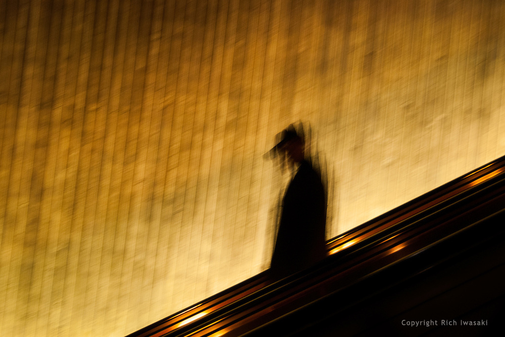 Blurred motion view of pedestrian descending escalator, Metro rail station, Washington, DC
