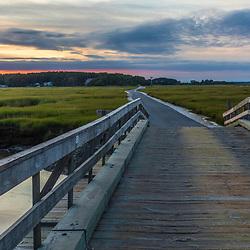 A wooden bridge crosses the salt marsh in Wellfleet Bay, Wellfleet, Massachusetts.