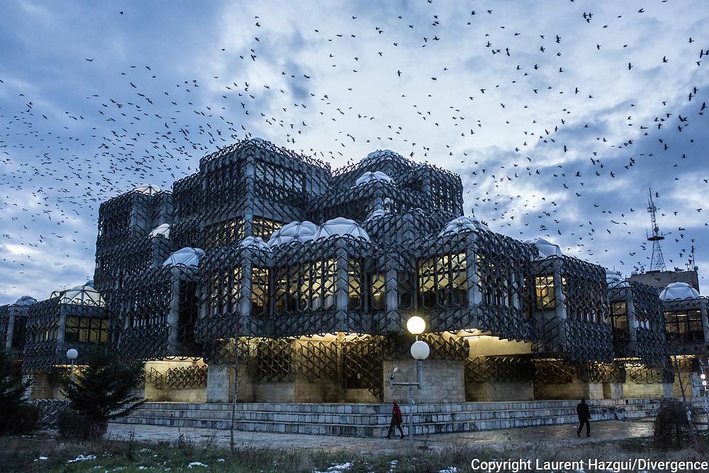 Décembre 2017. Kosovo : 10ème anniversaire de l'indépendance. La bibliothèque universitaire de Prishtina à l'architecture Yougoslave avec des centaines de merles qui volent en escadron enfin de journée Pristina. Prishtina.