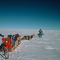 Led by distant Victor Boyarsky, a dogsled from the 1989-1990 Trans-Antarctica Expedition navigates across the vast polar plateau.