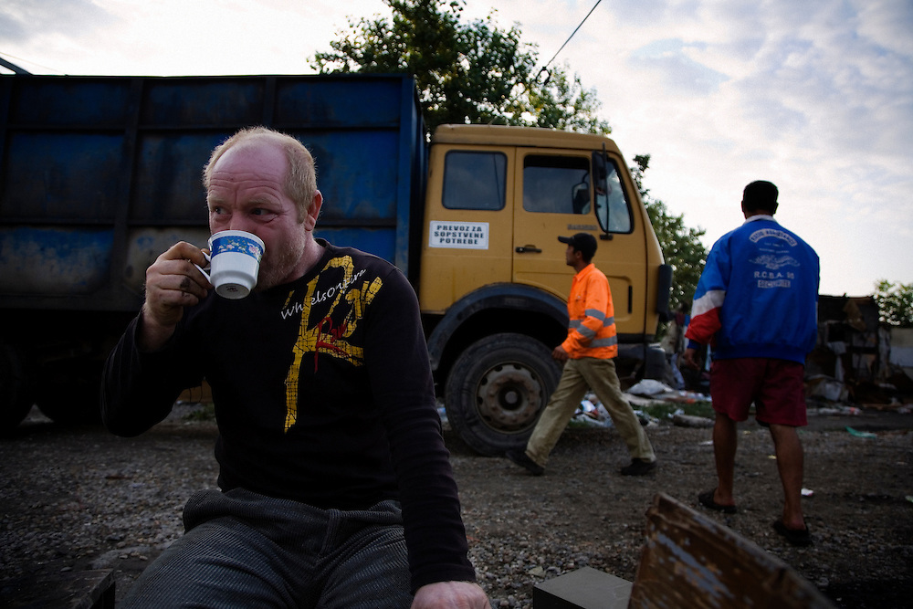 Stojan's father drinks his morning coffee in the Nova Gazela settlement as the first work crews arrive at 7:01am for the relocation of the camps.