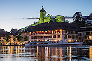 After sunset, Munot Castle is floodlit in green above a cruise boat reflecting in the Rhine River in Schaffhausen, Switzerland, Europe. Schaffhausen was founded where trading ships had to set anchor because Rhine Falls blocked further travel. Today, the popular Untersee Lake-Rhine boat trip from Schaffhausen to Kreuzlingen is nearly 50 km long. Schaffhausen's iconic circular fortress, was built by forced labor in 1564-1589 after the religious wars of the Reformation.