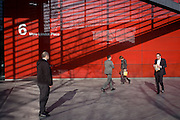 Diagonal shadows and the red theme of a modern office exterior at 6 More London, where a Londoners to and fro in the capital.