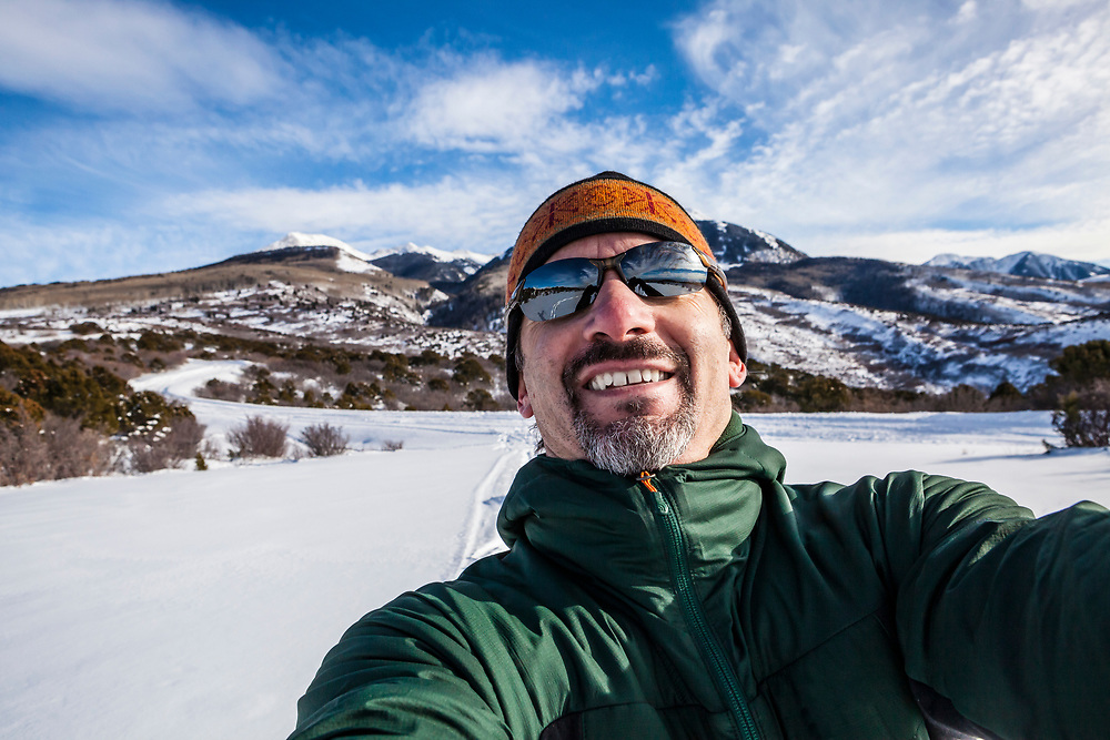 A middle aged man taking a selfie up on the foothills of the LaSal Mountains while cross country skiing, Southeastern Utah, USA.