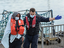 © Licensed to London News Pictures. 03/08/2021. Dover, UK. A  migrant is helped ashore by a Border Force officer at Dover Harbour in Kent after crossing the English Channel. Hundreds of migrants have made the crossing in recent weeks. Photo credit: Stuart Brock/LNP
