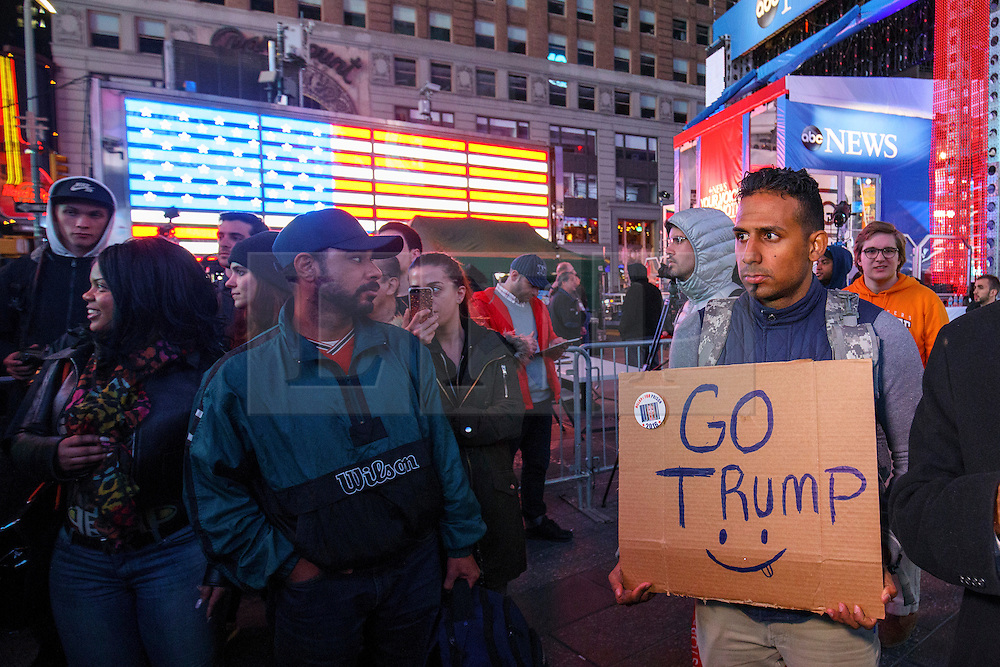 © Licensed to London News Pictures. 09/11/2016. New York CIty, USA. A man carrying a pro-Trump sign reacts to news that Donald Trump being elected as the next president of the United States, while gathering in Times Square, New York City, on Wednesday, 9 November. Photo credit: Tolga Akmen/LNP
