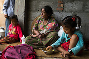 Monika (7, in red) and Aastha Baniya (6, in blue) sit with their grandmother Bhagawati Baniya (56) as she cradles their youngest sister Sapana Baniya (2 months) in their temporary home in Chautara, Sindhupalchowk, Nepal on 29 June 2015. The three girls lost their mother during the April 25th earthquake that completely levelled their house. Aastha was buried under the rubble together with her mother but Aastha survived. As their father Ratna Baniya (28) cannot care for the children on his own, SOS Childrens Villages has since been supporting the grandmother with financial and social support so that she can manage to raise the children comfortably and ensure that they will all be schooled. Photo by Suzanne Lee for SOS Children's Villages