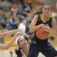 Jordan Joe (34) and Mckleigh Begaye (23) of Gallup battle for the loose ball near the sideline with Maya Trujillo (12) St. Pius X in Gallup on Wednesday. St. Pius won 53-43.