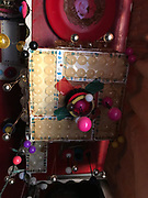 Red shelf above front window in grocery decorated with a hanging card board box with beads and bears nada red frizzbee glued to under side of shelf hangs above hook rug table- 3 ft by 8 in by 2 in thick- has lights and beads and more<br />