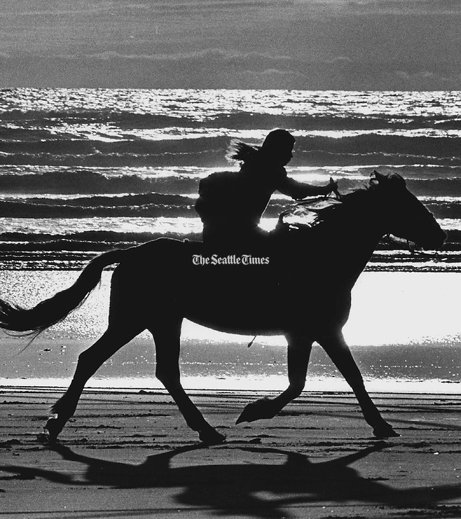 A young girl rides a horse on the beach, silhouetted by waves and sun. (The Seattle Times, 1988)