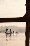 Young men in boat, taking photographs on the Irrawaddy River, near Mandalay, Myanmar