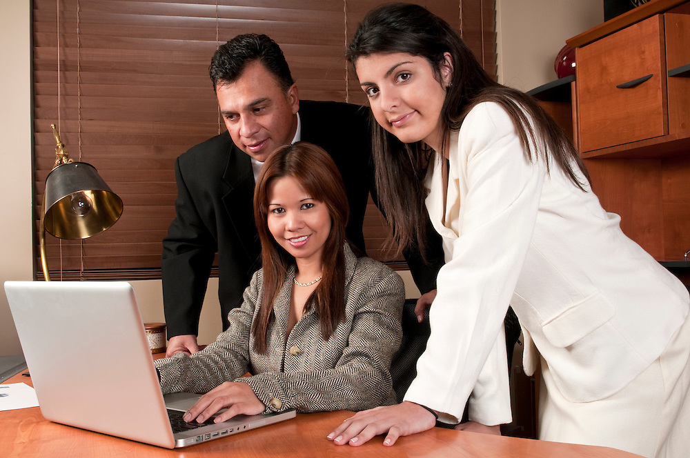Group of coworkers sharing information and looking at computer in small business.