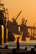 Man stands alone in silhouette at shipping port, Yangon River