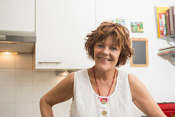 Portrait of a senior woman standing in the kitchen and smiling, Munich, Bavaria, Germany