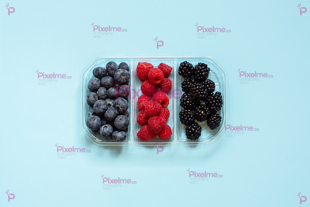 Flatlay group of fresh blueberries, raspberries and blackberries in a transparent plastic container isolated in a light blue background viewed from the top. Above view.
