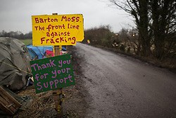 """© Licensed to London News Pictures . 24/01/2014 . Barton Moss Road , Manchester , UK . Sign reading """" Barton Moss . The front line against Fracking """" . Site of a protest camp on Barton Moss Road where anti-fracking demonstrators are based on an access road leading to an iGas fracking site as today (24th January 2014) Greater Manchester Police announce two further arrests from the ongoing protest after reporting that a security guard was threatened and assaulted on Barton Moss Road on Monday (20th January 2014) . Photo credit : Joel Goodman/LNP"""