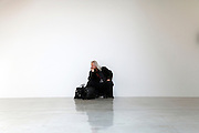 person against a white wall in a modern art Gallery listening and thinking