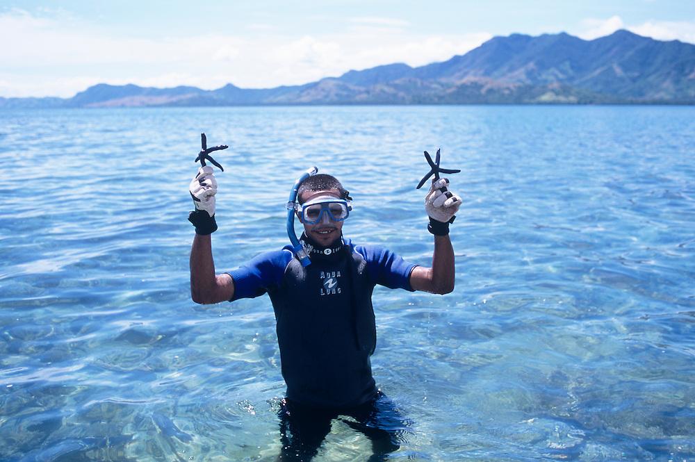 Fiji Islands, Nukubati Island Resort, staff diver with Blue Sea Star starfish, Linckia laevigata