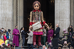 London, UK. 23rd October, 2021. Little Amal, a giant puppet of a Syrian refugee girl fleeing conflict, leaves St Paul's Cathedral after being welcomed by the dean Dr David Ison and a crowd including many children. The 3.5-metre puppet, which is nearing the end of an 8,000km journey from the Turkish-Syrian border to Manchester in support of refugees, climbed the steps of St Paul's Cathedral to present a wood carving of a ship at sea from St Paul's birthplace at Tarsus in Turkey to the dean.