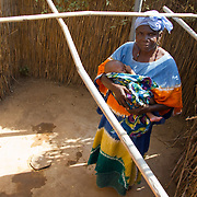 A happy grandmother stands with her newly-born grandchild by her family's new latrine. Its construction was part of a project led by Koumbadiouma's Peace Corps volunteer, Rachael Honick. Kolda, Senegal.