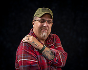 """Twenty-five year Army veteran Terry shows off his """"IGY6"""" tattoo. IGY6 stands for """"I Got Your Six (six o'clock, means back). The colors also carry a meaning. Teal is for PTSD awareness, black is for the heavy hearts that many of us carry, those who suffer from PTSD and those who have lost loved ones to suicide because of PTSD.  (Photo © Andy Manis)"""